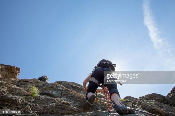 mountain climbers make their way up rock face - zakelijke kleding stock pictures, royalty-free photos & images