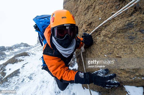 Mountain climbers using climbing ropes to scale a cliff overlooking the Ross Ice Shelf.