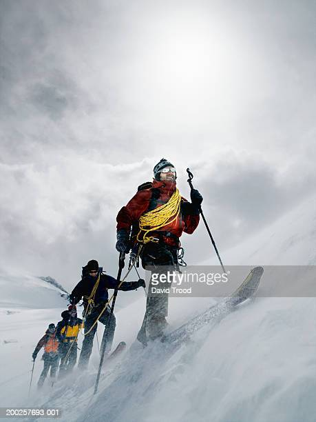 Mountain climbers walking through blizzard, linked together with rope