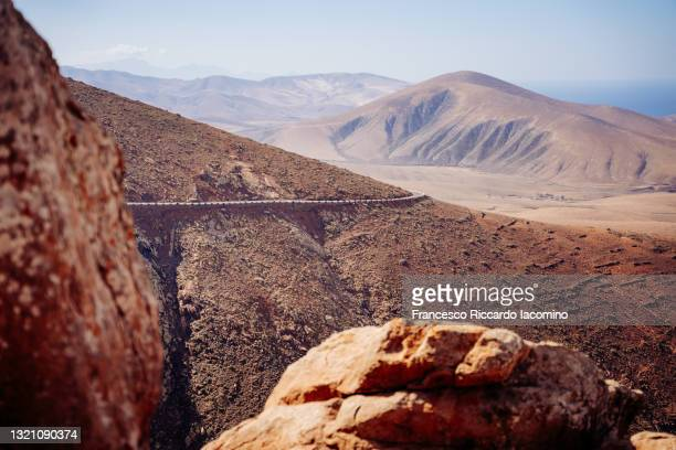 mountain desertic landscape, blue sea in background. fuerteventura, canary islands - francesco riccardo iacomino spain foto e immagini stock