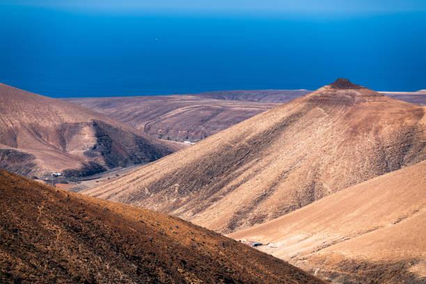 mountain desertic landscape, blue sea in background. Fuerteventura, Canary Islands