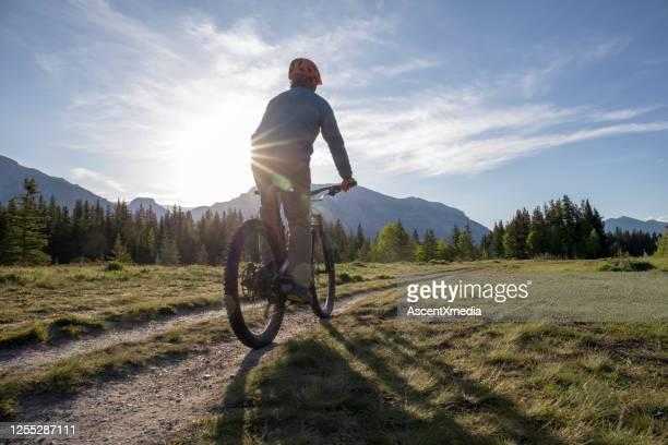 山の電子バイカーは草の牧草地を通って乗る - forward athlete ストックフォトと画像