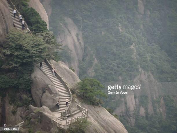 Mountain edge hiking along Huangshan / Yellow mountain stairs by canyon cliff, China