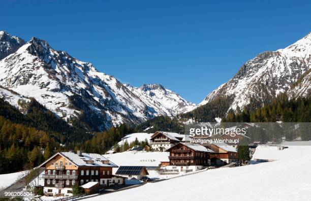 mountain farms in a snow-capped mountain landscape, high tauern national park, kalser tal valley, kals am grossglockner, tyrol, austria - carinthia stock pictures, royalty-free photos & images