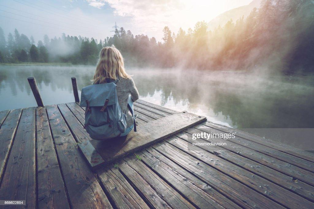 Mountain girl enjoying morning fog from lake pier, sun rising : Stock Photo
