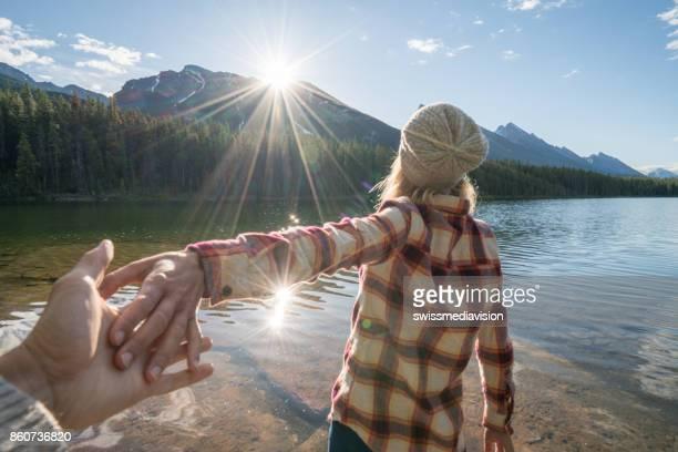 Mountain girl leading boyfriend to lake