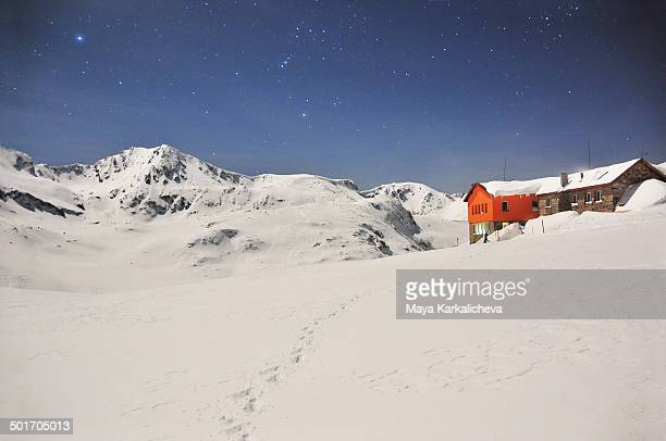 CONTENT] Mountain hut surrounded by snow at clear stary night with peaks in background Rila mountain National Park Bulgaria