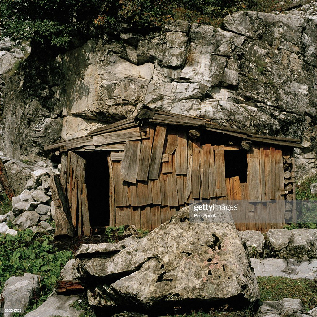 A mountain hut, used mainly for storing tools. Although she has a house in Tplan about 4 days walk from here, Jemine Zecja, aged 70, has been staying in stone or wood huts like this one throughout most of her life as a shepheard. In the patriarchal rural Albanian society the age-old tradition of the Virgjineshe ('sworn virgins') gives women the choice of taking on a male identity in order to enjoy male privileges. Becoming a 'sworn virgin' means to vow lifelong celibacy and to turn into a surrogate son to her father. The reasons for taking the vow are a lack of sufficient men in a family to carry out the men's work, or the lack of a headstrong man to become the head of the family. A woman might also escape an unwanted arranged marriage, without damaging family honour or she might want to be independent to travel and work as she pleases. Often the decision is made by the family head e.g. her father, grandfather or uncle. The girl or woman then acquires a male name, male clothes and a male haircut. With the new status she obtains all the male privileges, such as inheriting property, making decisions within the family and the community, being able to carry weapons, taking part in blood feuds and socializing freely with men. They are completely accepted and addressed as men by other members of their community and often behave more manly than the men. The occurrence of Tobelija is most common in and around Bjesket e Nemuna (The Accursed Mountains) covering the northern regions of Albania and bordering regions of Montenegro and Kosovo.