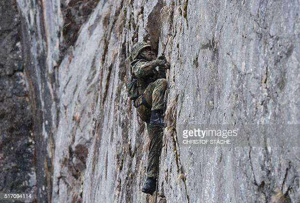A mountain infantry soldier climbs during an exercise of the mountain infantry brigade 23 of the German Bundeswehr at an exercise area near the...