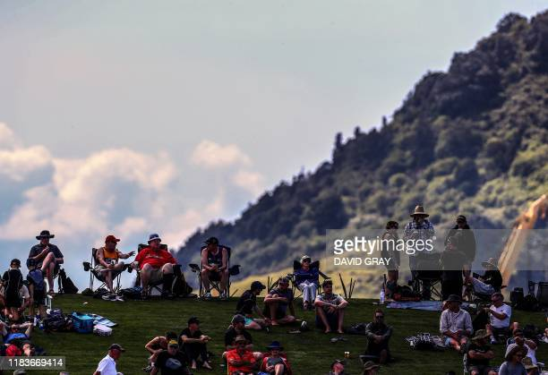 A mountain is visible behind members of the crowd as they watch the first day of the first cricket Test between England and New Zealand at Bay Oval...