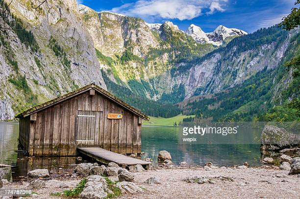 mountain lake fishing hut surrounded high mountain-range - königssee bavaria stock photos and pictures