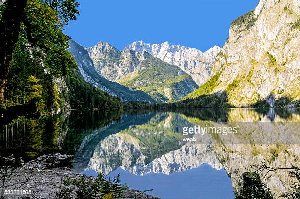 mountain lake surrounded mountain-range dramatic reflection - königssee bavaria stock photos and pictures