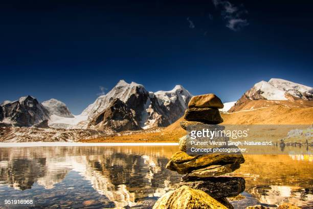 mountain lake with holy stones stacked together - northeast india stock photos and pictures