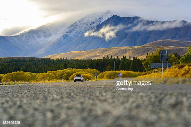 Mountain landscape with road and blue sky, New Zealand.