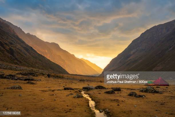 mountain landscape with trekking camp in mountain valley under moody sunset sky, cordillera huayhuash, peru, south america, queropalca, huanuco region - light natural phenomenon stock pictures, royalty-free photos & images