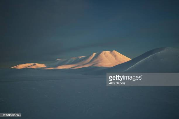 a mountain lit by sunrise. - alex saberi stock-fotos und bilder