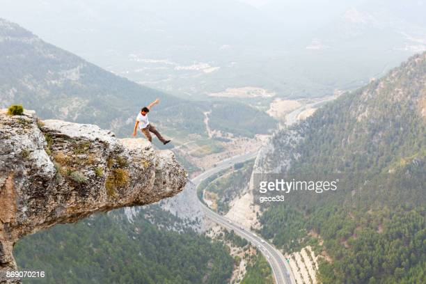 mountain man success concept on high rock - inequality stock photos and pictures
