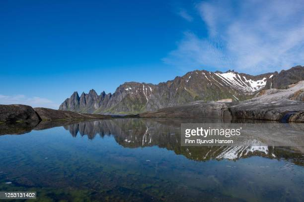 mountain oksehornet, djevelens tanngard reflecting in the water at tungeneset at the island of senja in northern norway - finn bjurvoll stock pictures, royalty-free photos & images