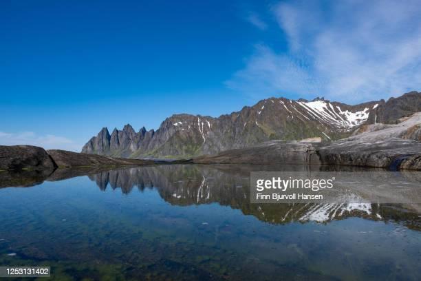 mountain oksehornet, djevelens tanngard reflecting in the water at tungeneset at the island of senja in northern norway - finn bjurvoll stockfoto's en -beelden