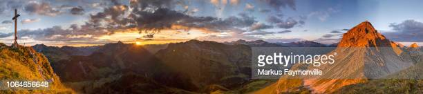 夜明け燃えるようなオレンジで山のパノラマ - フォアアールベルク州 ストックフォトと画像