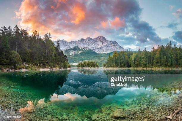 mountain peak zugspitze summer day at lake eibsee near garmisch partenkirchen. bavaria, germany - landscape scenery stock photos and pictures