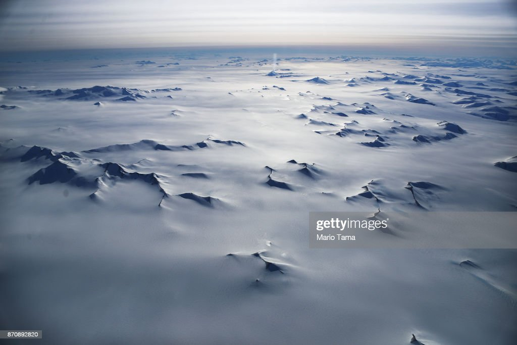 Mountain peaks are seen from NASA's Operation IceBridge research aircraft in the Antarctic Peninsula region, on November 4, 2017, above Antarctica. NASA's Operation IceBridge has been studying how polar ice has evolved over the past nine years and is currently flying a set of nine-hour research flights over West Antarctica to monitor ice loss aboard a retrofitted 1966 Lockheed P-3 aircraft. According to NASA, the current mission targets 'sea ice in the Bellingshausen and Weddell seas and glaciers in the Antarctic Peninsula and along the English and Bryan Coasts.' Researchers have used the IceBridge data to observe that the West Antarctic Ice Sheet may be in a state of irreversible decline directly contributing to rising sea levels. The National Climate Assessment, a study produced every 4 years by scientists from 13 federal agencies of the U.S. government, released a stark report November 2 stating that global temperature rise over the past 115 years has been primarily caused by 'human activities, especially emissions of greenhouse gases'.