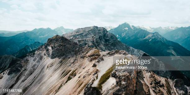 mountain peaks under cloudy sky - horizontal stock-fotos und bilder