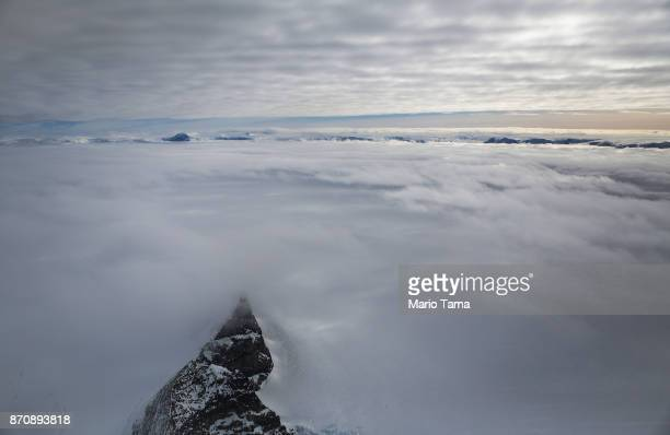 A mountain peeks through clouds and ice as seen from NASA's Operation IceBridge research aircraft near the coast of the Antarctic Peninsula region on...
