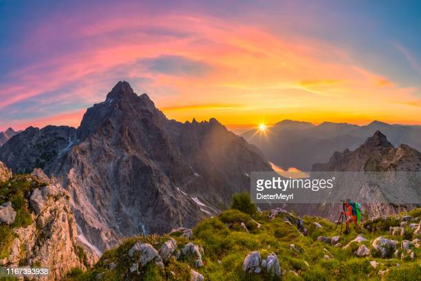 mountain photographer at glory sunrise with view to watzmann and summit cross of mount großer hundstod - bavarian alps stock pictures, royalty-free photos & images