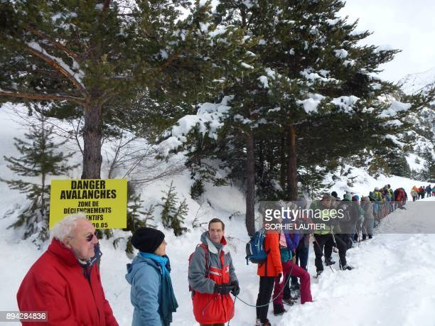 Mountain professionals stand linked together with ropes as they take part in a rally to warn of the dangers to migrants in crossing passes in the...
