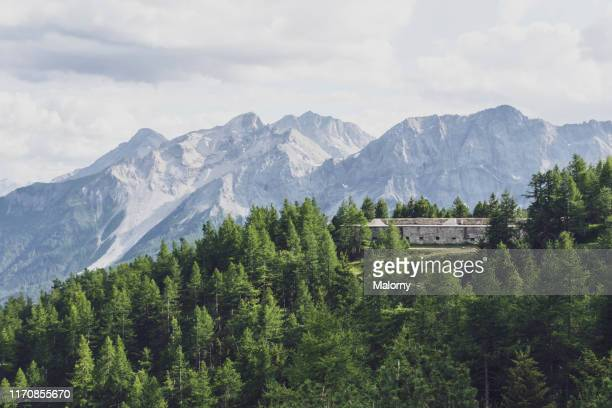 mountain range and old stone building or fort on mountain top. - バルドネキア ストックフォトと画像