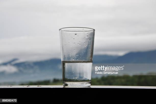 A mountain range and sky scenery viewed through a cup of water