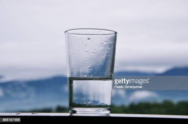 A mountain range and sky scenery viewed through a glass of water