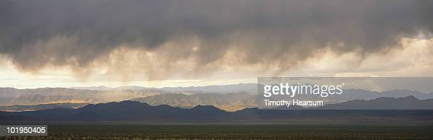 mountain range in sun, storm clouds above - timothy hearsum stock photos and pictures