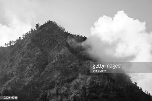 mountain range lying adjacent to mount bromo. with a perfect triangular mountain top, rising from a sea of volcanic ash surrounding the caldera. - shaifulzamri stock-fotos und bilder