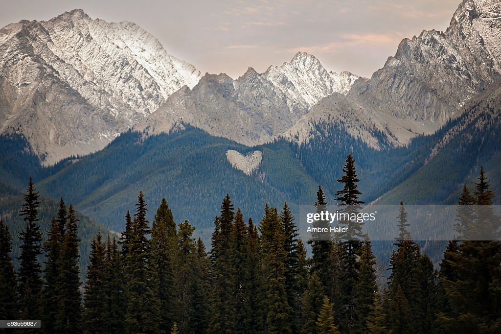 A natural heart shape in the snow peaked Rocky Mountains British Columbia Canada. Photo taken at sunset
