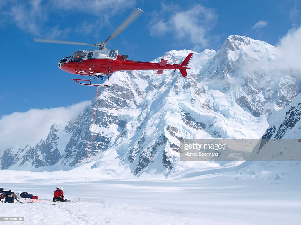 Mountain Ranger waiting to be picked up by a helicopter in Denali National Park, Alaska. Mount Hunter is in the background. : Stock Photo