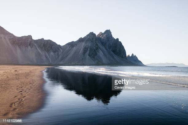 mountain reflection in iceland on the beach - county cavan stock photos and pictures