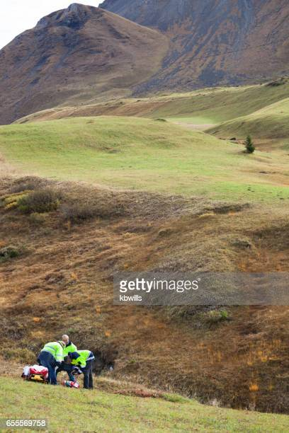 mountain rescue team with stretcher and gurney on mountainside in Swiss Alps