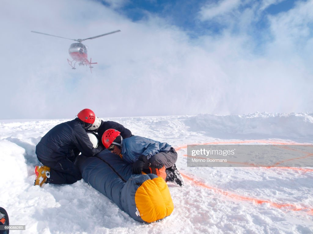 Mountain Rescuers are protecting a victim for the down wind of the landing helicopter at 14.000 foot on Denali, formerly known as Mount McKinley.  : Foto de stock