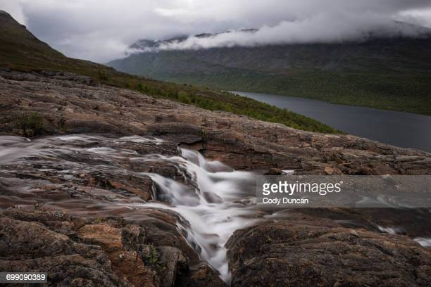 mountain river flows above lake teusajaure, kungsleden trail, lapland, sweden - norrbotten province stock photos and pictures
