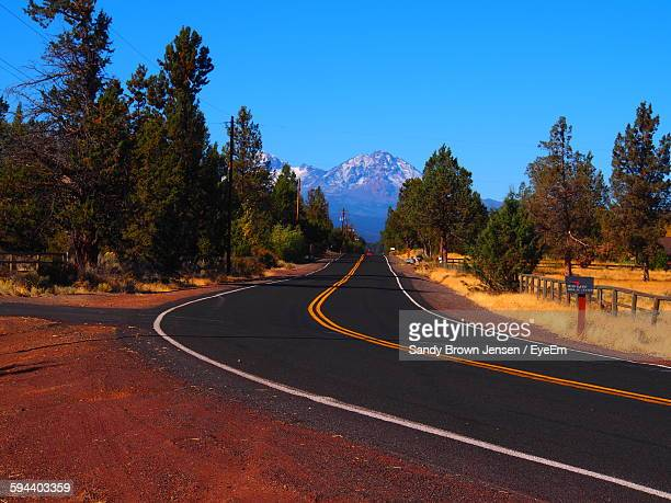 Mountain Road Amidst Trees Against Clear Blue Sky