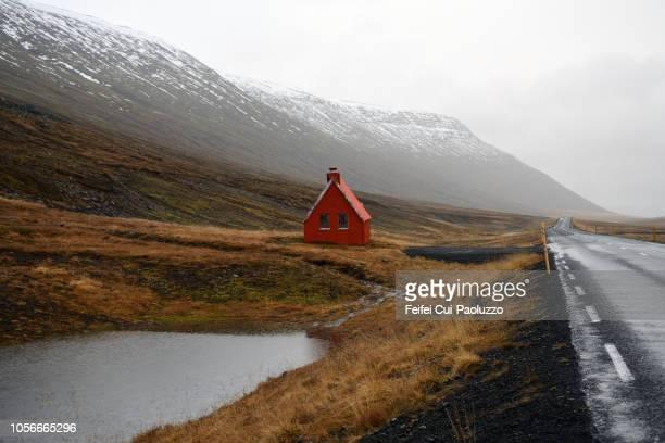 mountain road and rescue cabin near egilsstadir in eastern iceland - abgeschiedenheit stock-fotos und bilder