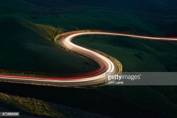mountain road at night.long exposure. - vehicle light stock photos and pictures