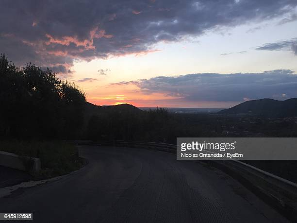 Mountain Road By Trees Against Cloudy Sky During Sunset