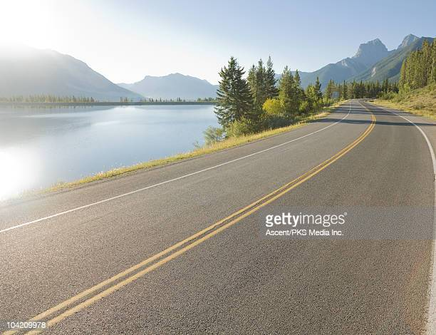 Mountain road curves around lake, in mountains