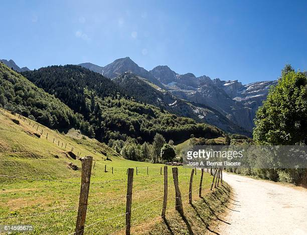 Mountain road that runs through the center of a valley to the circus of Gavarnie. Hautes Pyrenees. France. World Heritage Site by UNESCO.