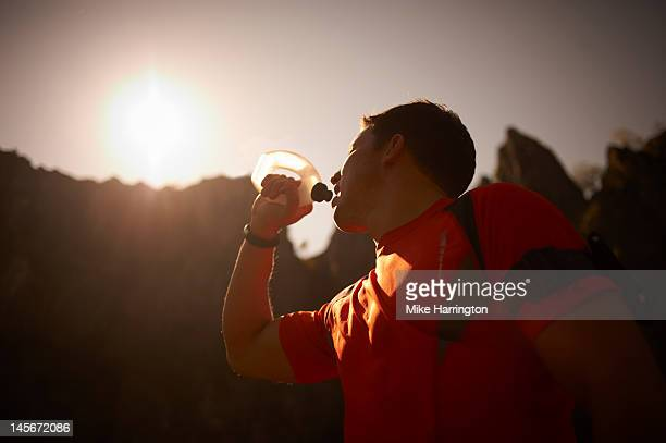 mountain runner drinking from sports bottle - one mid adult man only stock pictures, royalty-free photos & images