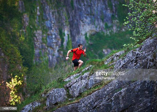 mountain runner running up steep incline - performance stock pictures, royalty-free photos & images