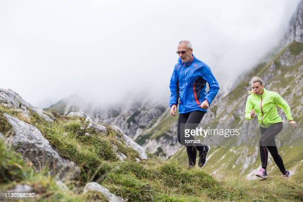 mountain running couple - uphill stock pictures, royalty-free photos & images